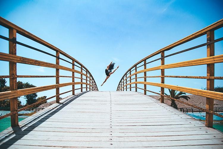 Uma bailarina saltando em uma ponte, um movimento de dança.